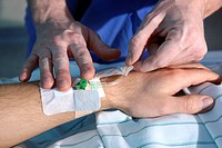 Male nurse placing a venous access, intensive care unit, hospital