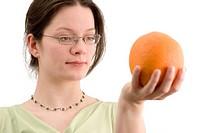 Junge Frau hält Orange in ihrer Hand