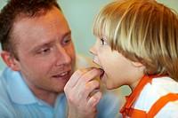 Vater füttert seinen Sohn mit einem Bonbon