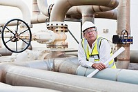 Worker on pipes at chemical plant