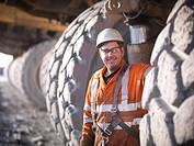 Worker standing by trucks in coal mine