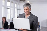 Germany, Bavaria, Munich, Mature man using laptop, colleagues working in background