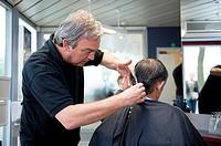 A barber giving a male customer a haircut.
