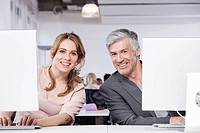 Germany, Bavaria, Munich, Man and woman using computer in office, smiling, portrait