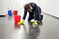 Businessman scrubbing office floor