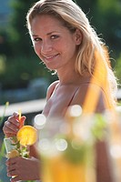 Austria, Salzburg County, Young woman with drink near pool