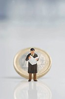 Businessman figurine holding newspaper in front of euro coin