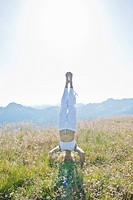 Austria, Salzburg County,, Young woman doing headstand in alpine meadow