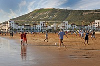 Playing football on Agadir Beach, hill with the words, Allah, al-Watan, al-Malik, meaning Allah, the Homeland, the King, Morocco, Africa