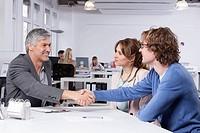 Germany, Bavaria, Munich, Men shaking hands at table