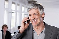 Germany, Bavaria, Munich, Mature man on mobile phone, colleagues working in background