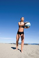 Girl practicing and playing volleyball on the beach at Spanish Banks park in Vancouver, British Columbia.