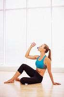 Woman in sports bra drinking water