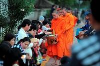 Moenche am fruehen Morgen beim einsammeln von Reis in der Altstadt von Luang Prabang in Zentrallaos von Laos in Suedostasien.