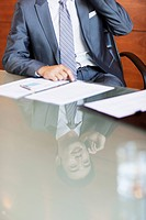 Reflection of businessman on cell phone in conference room