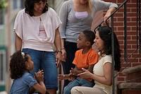 Two Hispanic women smiling with their children
