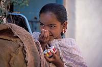 Girl applying a coloured bindi, Badami, Karnataka, South India, India, Asia