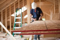 Carpenter using a circular saw on particle board in a house under construction