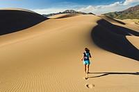 Hispanic woman running on sand dune