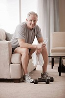 Caucasian man in living room drinking water after exercise