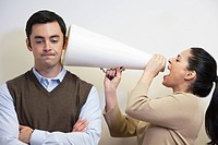 Businesswoman shouting with megaphone into co_worker´s ear