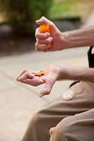 Man with Friedreichs Ataxia holding pills with degenerated hands