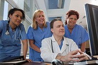 Doctor and nurses consulting on a computer in hospital