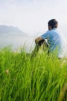 Man sitting on grass at Lake Lucerne, Switzerland, Europe