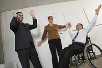 Low angle view of three business executives cheering in an office