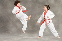 Mid adult woman practicing karate with a young woman
