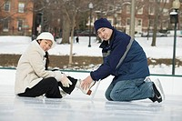 Portrait of a young man tying ice skate laces of a young woman