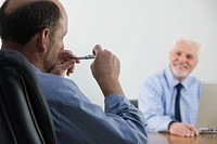 Two businessmen talking in conference room