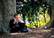 Stressed businessman working on a laptop in a park