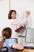 Students in computer classroom writing on whiteboard