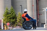 Facilities engineer in a wheelchair studying outdoor bulk storage tanks