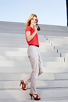 Blond woman with coffee to go on stairs