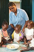 Infants eating with a children's nurse in an orphanage near Bukoba, Tanzania, Africa