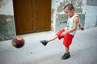 boy playing football on a village, Ludiente, Castellón, Spain