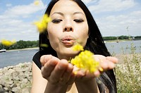 Germany, Young woman blowing blossoms at Rhine riverside