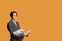 Mid adult woman holding stack of newspapers
