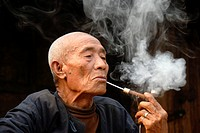 Male smoker, portrait, indulgence, old man of the Mouchi ethnic group smoking a pipe, smoke lingering in the air, Ban Mouchi Kaw village, Samphan dist...