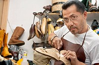 Portrait of a skilled cobbler cutting shoe sole in workshop