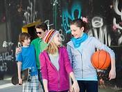 Four happy teenage friends walking at graffiti wall