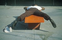 Homeless black man sleeping on a park bench