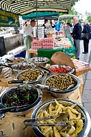 Fresh produce on a stall at an outdoor Farmers market, customer and stallholder in the background,