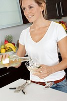 Woman In Kitchen Pouring White Wine