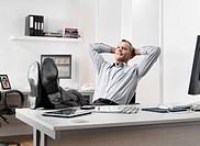 Businessman resting feet on desk