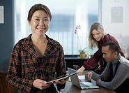 Japanese businesswoman in office holding digital tablet