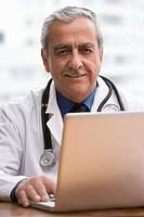 Hispanic doctor using laptop