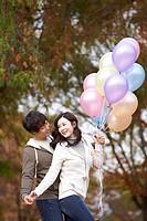 Young Couple On Foot Bridge Holding Balloon In Autumn